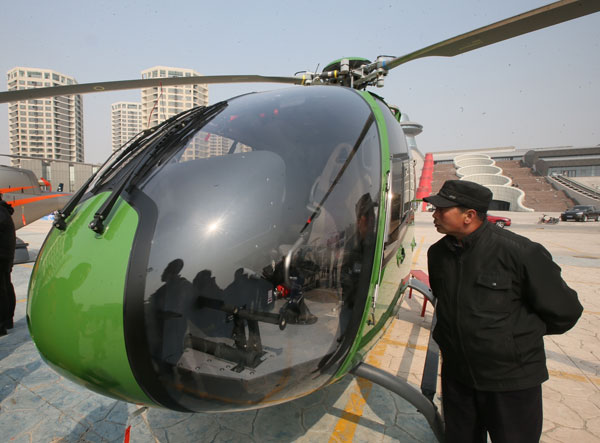 A visitor checks a helicopter on sale at a private aircraft store in Beijing on Saturday. JIANG GUIJIA / FOR CHINA DAILY